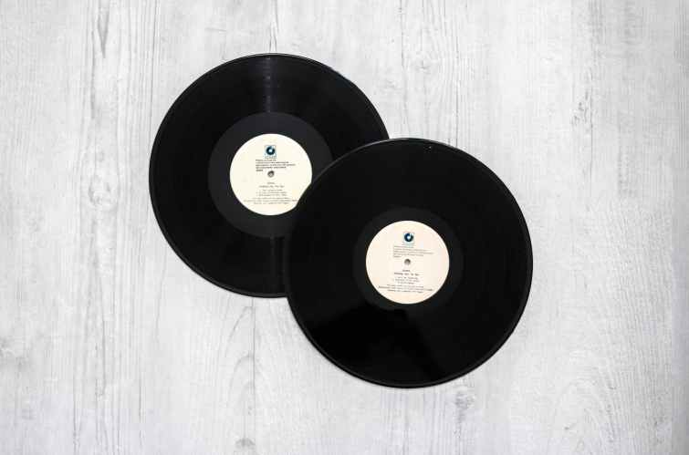 photography of vinyl records on wooden surace